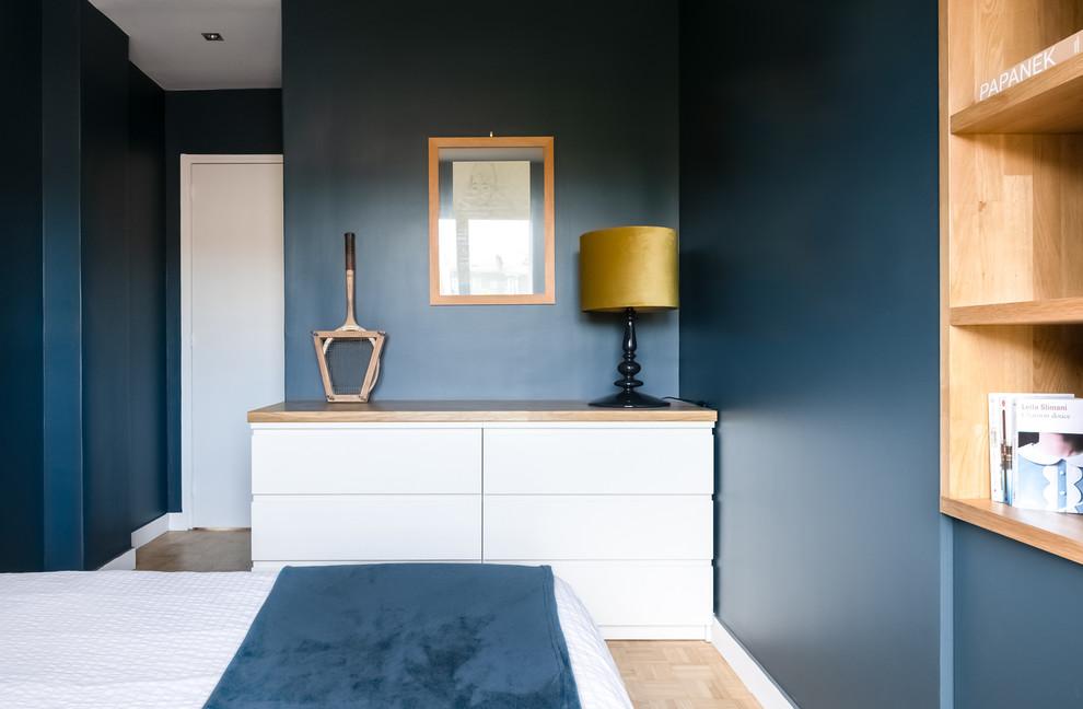 Réalisation d'une chambre parentale design de taille moyenne avec un mur bleu, un sol en bois clair, aucune cheminée et un sol beige.