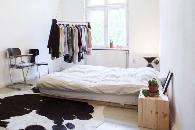 Выдающиеся фото от архитекторов и дизайнеров интерьера: спальня среднего размера в скандинавском стиле с белыми стенами и деревянным полом без камина для хозяев