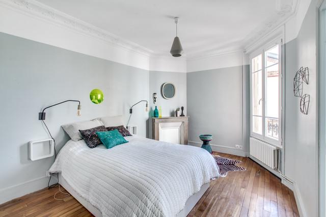 Exemple d'une chambre chic avec un mur bleu, un sol en bois brun et une cheminée standard.
