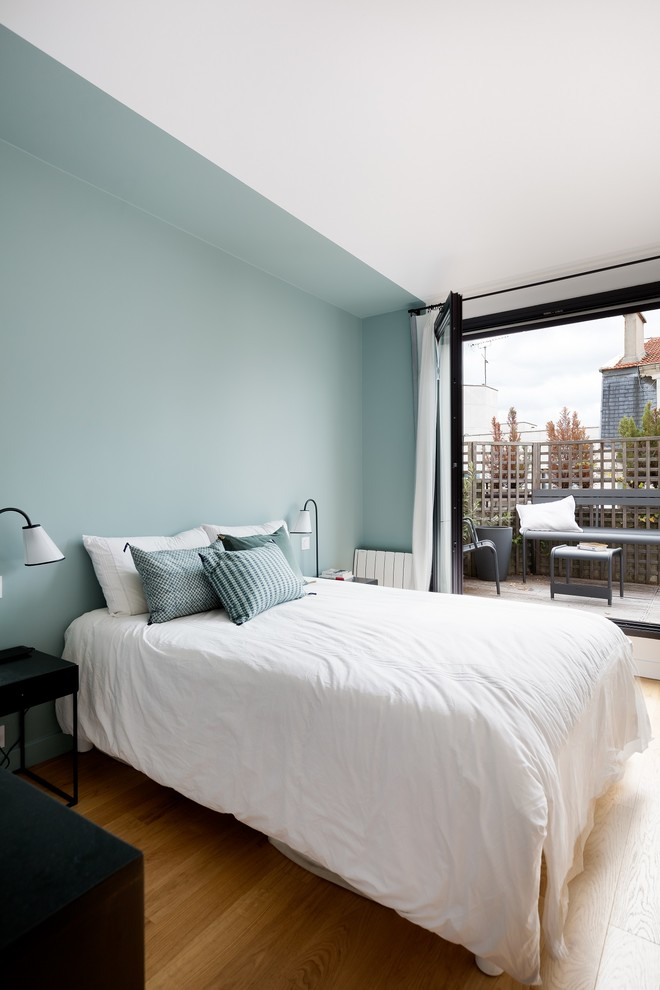 Inspiration for a contemporary light wood floor bedroom remodel in Paris with blue walls and no fireplace