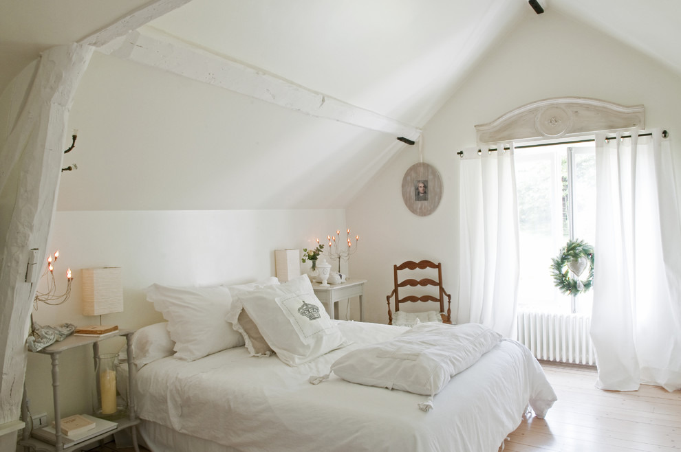 Example of a cottage chic light wood floor bedroom design in Paris with white walls