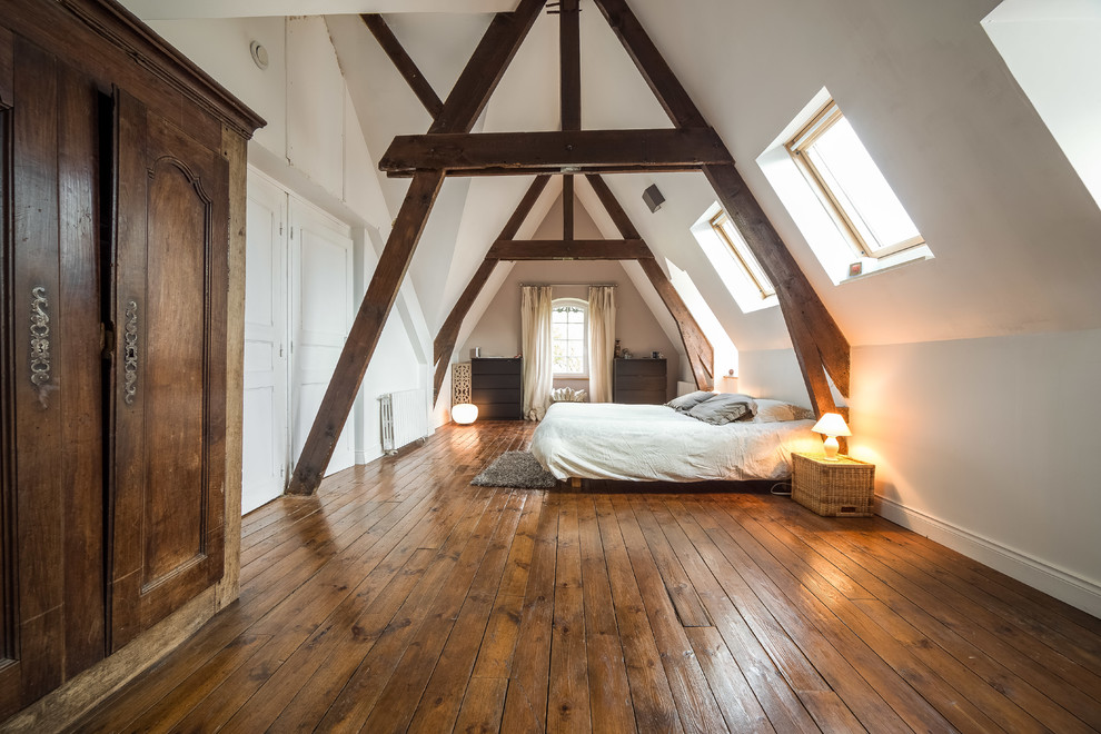 Example of a cottage medium tone wood floor bedroom design in Rennes with white walls