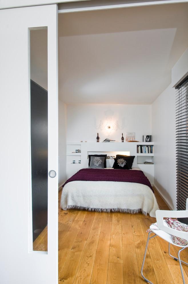 Bedroom - contemporary medium tone wood floor bedroom idea in Paris with white walls