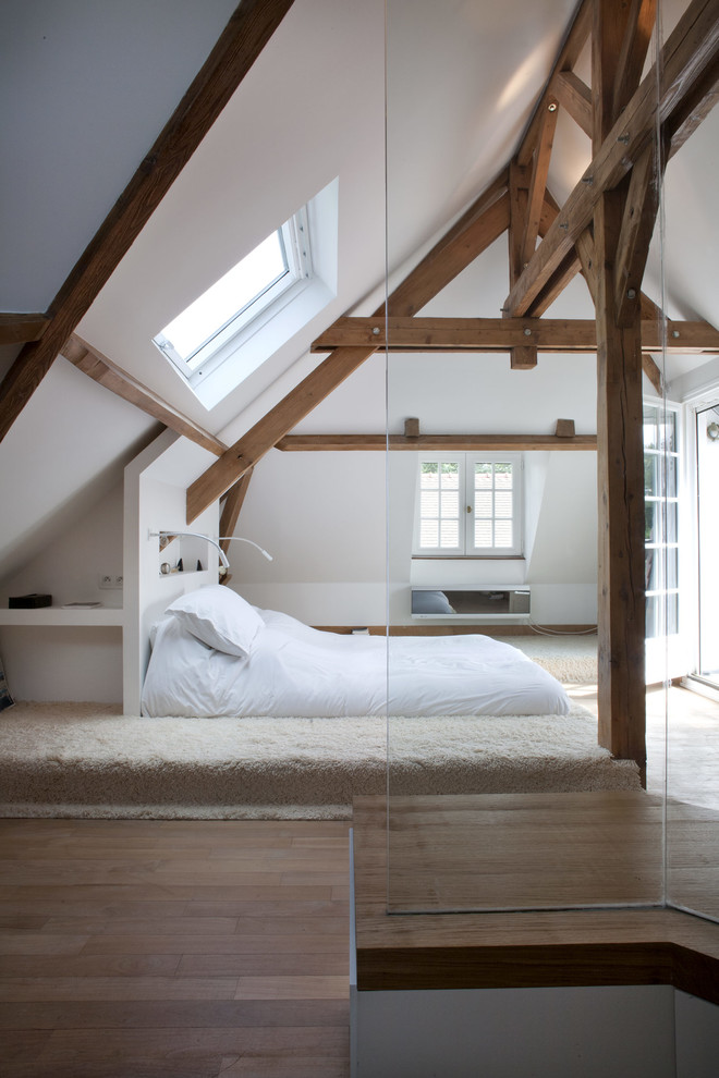 Inspiration for a mid-sized rustic loft-style medium tone wood floor bedroom remodel in Paris with white walls