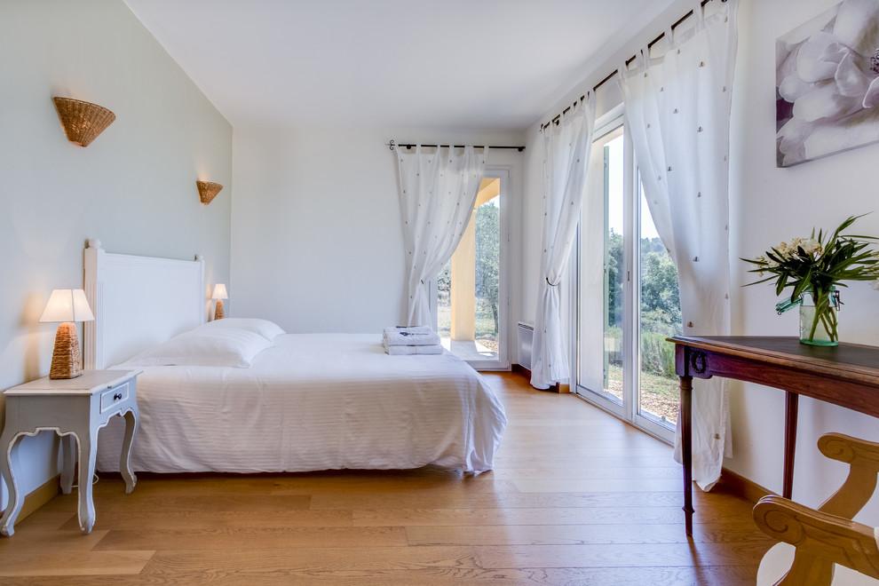 Idée de décoration pour une grand chambre d'amis tradition avec un mur blanc, un sol en bois brun et aucune cheminée.