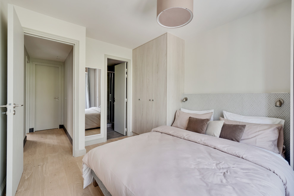 Inspiration pour une chambre d'amis design avec un mur blanc, un sol en bois clair et un sol beige.