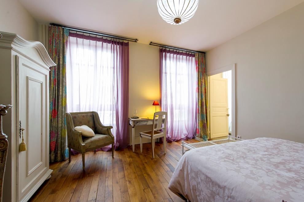 Idées déco pour une chambre parentale classique avec un mur beige et un sol en bois brun.