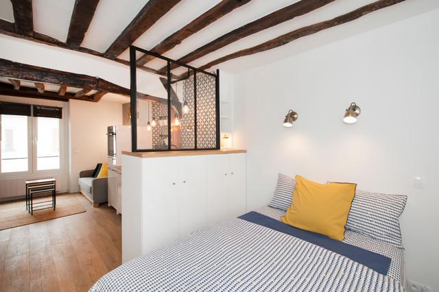 Idées déco pour une chambre parentale contemporaine de taille moyenne avec un mur blanc, un sol en bois brun et un sol beige.
