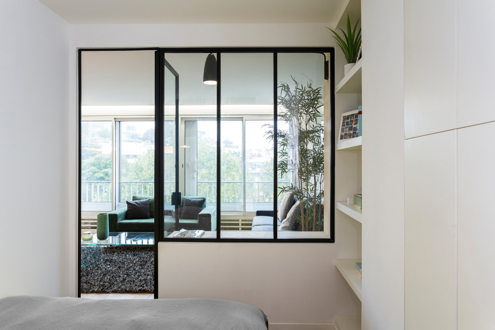 Example of a small danish master light wood floor bedroom design in Paris with white walls