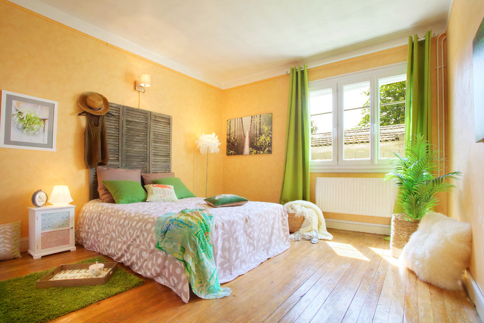 Mid-sized farmhouse master light wood floor bedroom photo in Toulouse with yellow walls