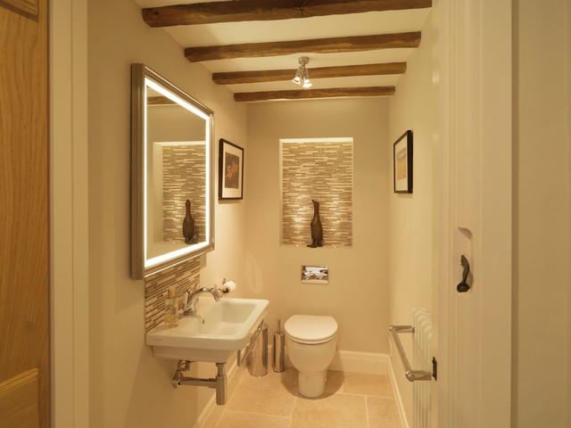 Example of a small cottage beige tile and glass tile limestone floor powder room design in Hampshire with a wall-mount sink, beige walls and a one-piece toilet
