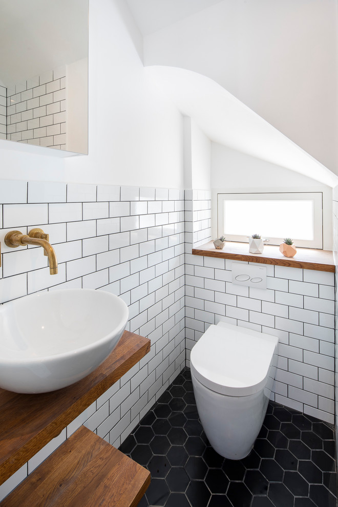 Example of a small danish white tile and subway tile black floor powder room design in London with white walls, a vessel sink, wood countertops, brown countertops and a wall-mount toilet