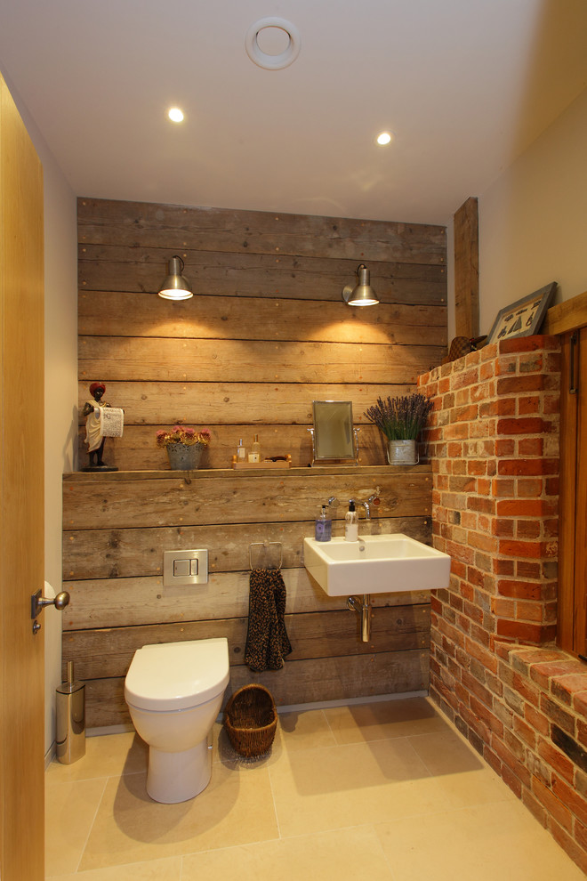 Example of a mid-sized mountain style powder room design in Hampshire with a wall-mount sink and a one-piece toilet