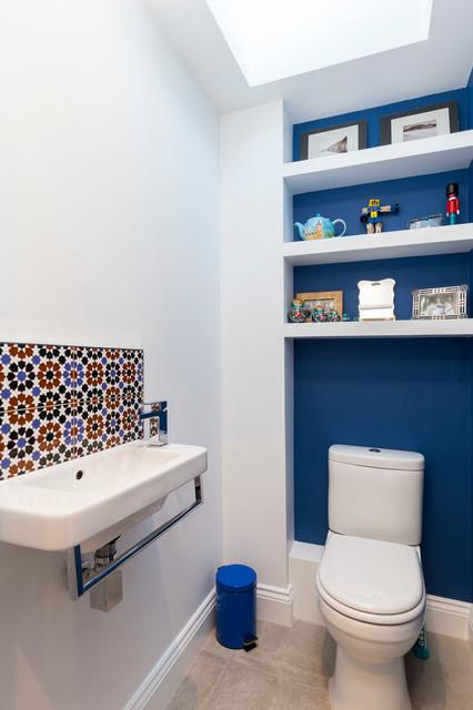 Réalisation de petits WC et toilettes tradition avec un WC séparé, un carrelage multicolore, un mur bleu, un lavabo suspendu et des portes de placard blanches.