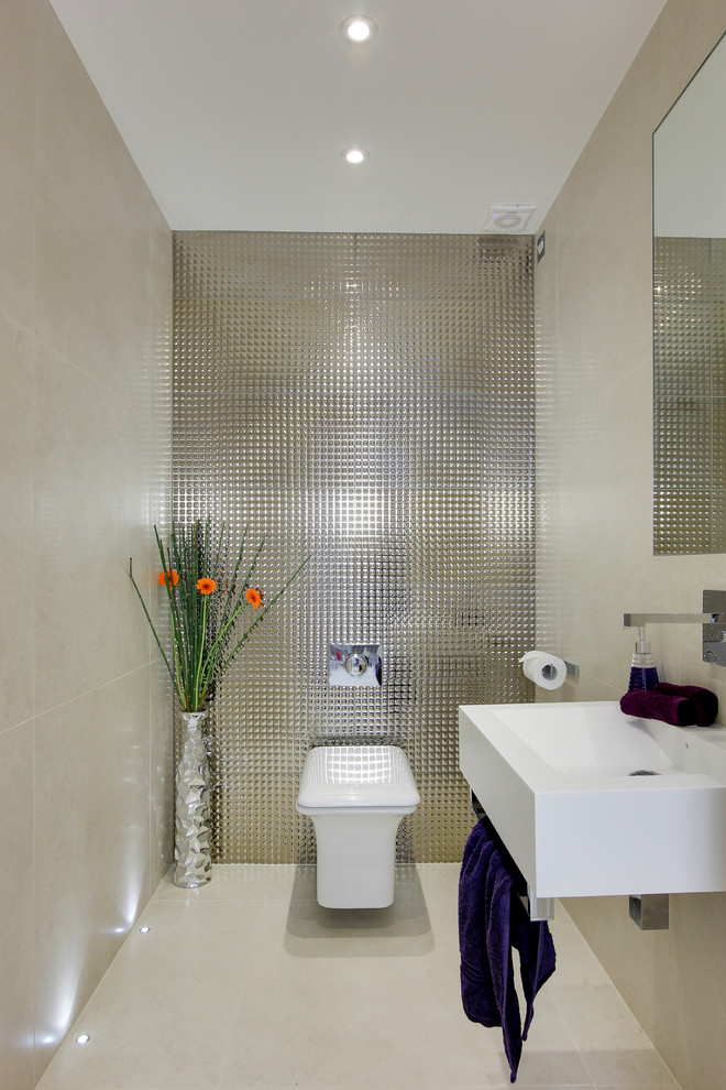 Example of a small trendy metal tile porcelain tile powder room design in Hertfordshire with a wall-mount sink and a wall-mount toilet