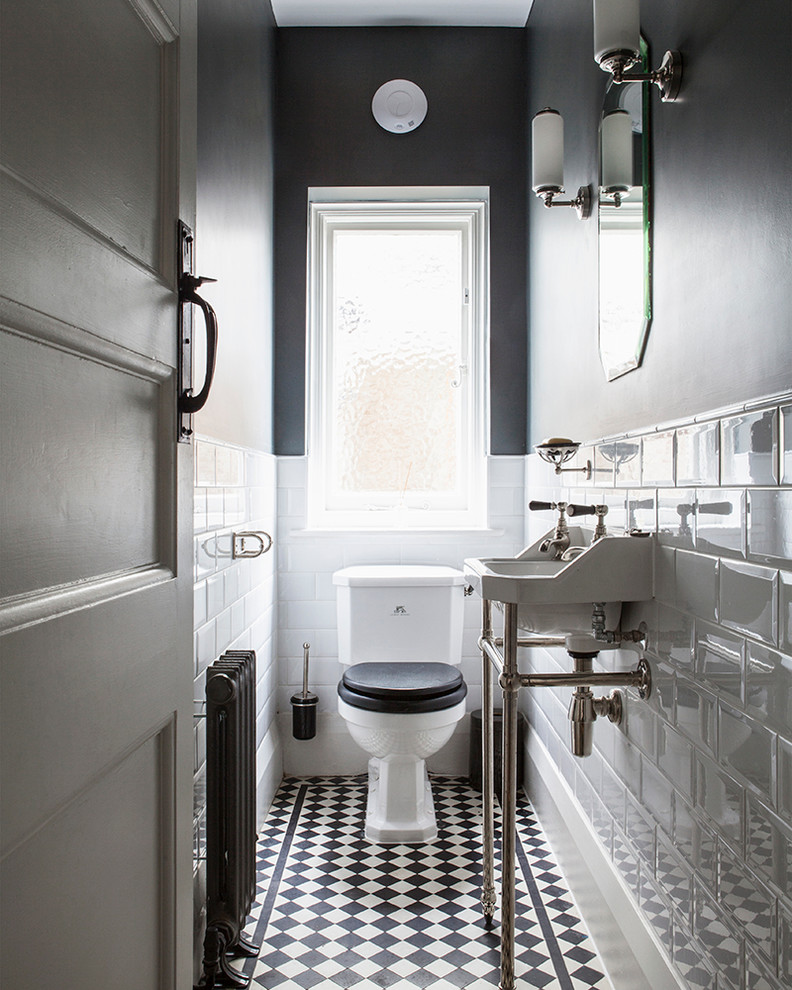 Example of a small classic black and white tile and white tile porcelain tile and multicolored floor powder room design in Sussex with gray walls, a console sink and a two-piece toilet