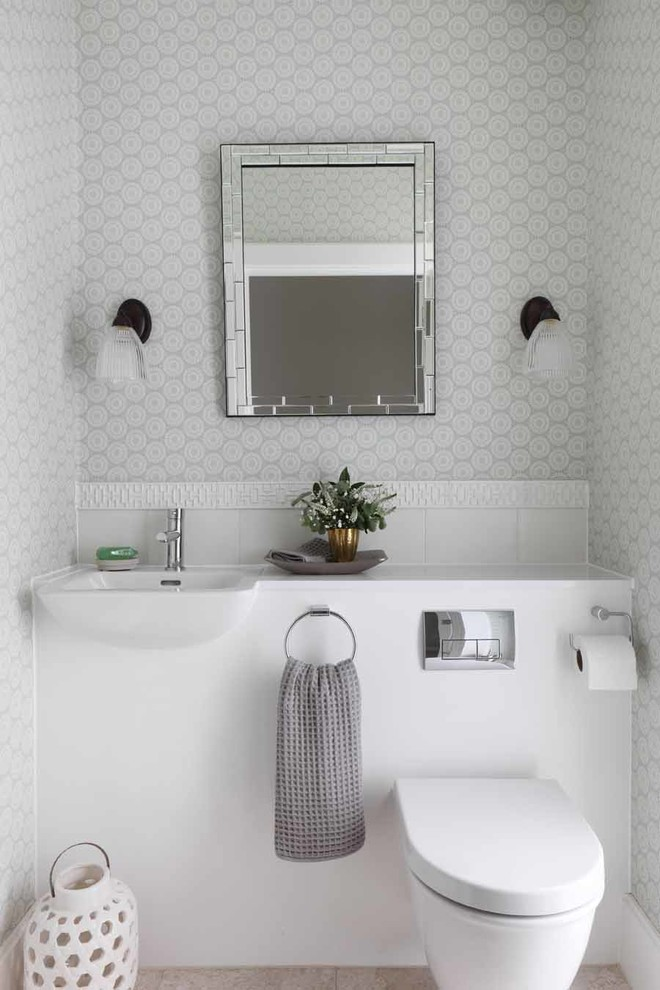 Trendy powder room photo in London with an integrated sink, a wall-mount toilet, gray walls and white countertops