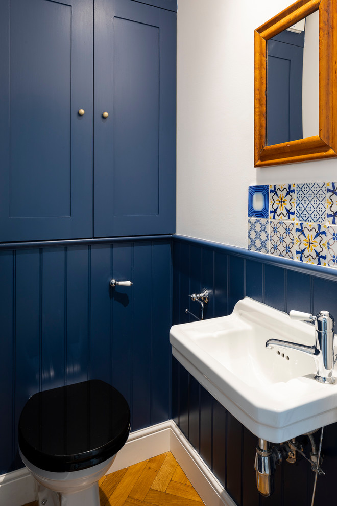 Ornate powder room photo in London with shaker cabinets