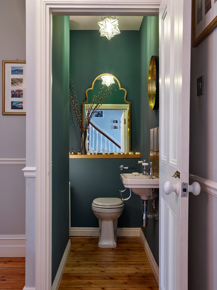 Inspiration for a small transitional medium tone wood floor and brown floor powder room remodel in Other with a one-piece toilet, green walls and a wall-mount sink