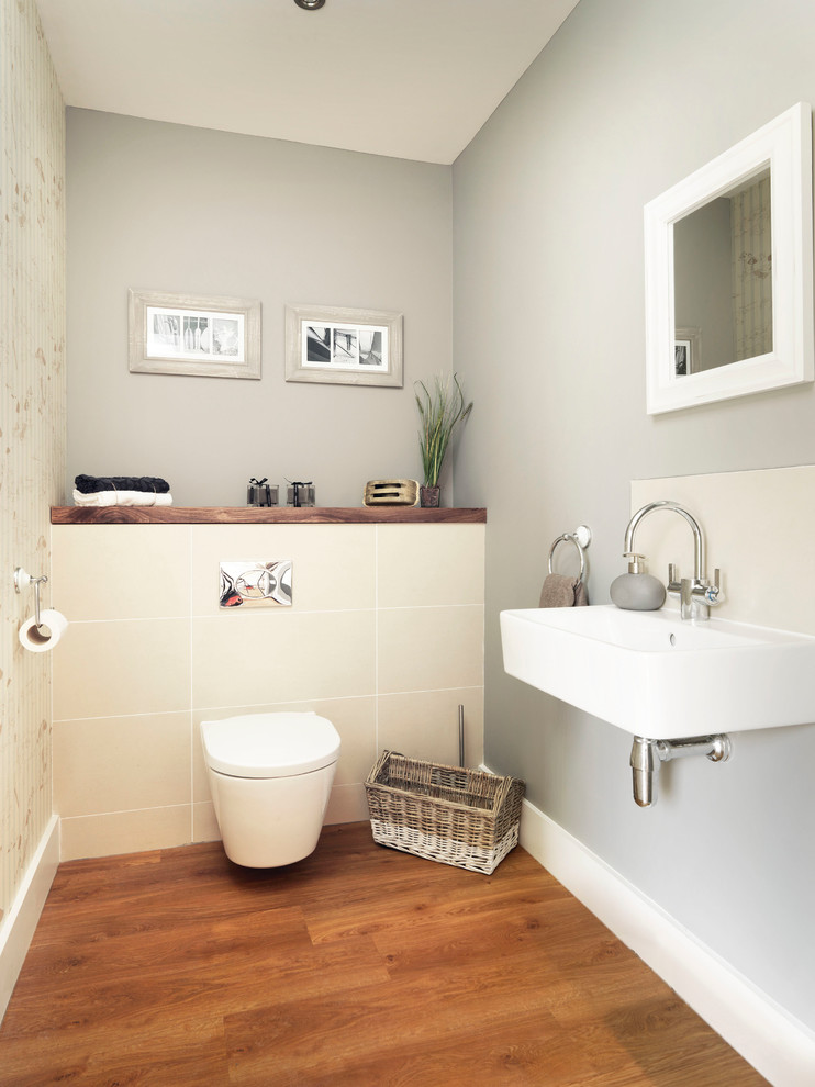Powder room - small coastal beige tile and ceramic tile medium tone wood floor powder room idea in Hampshire with a wall-mount toilet, gray walls and a wall-mount sink