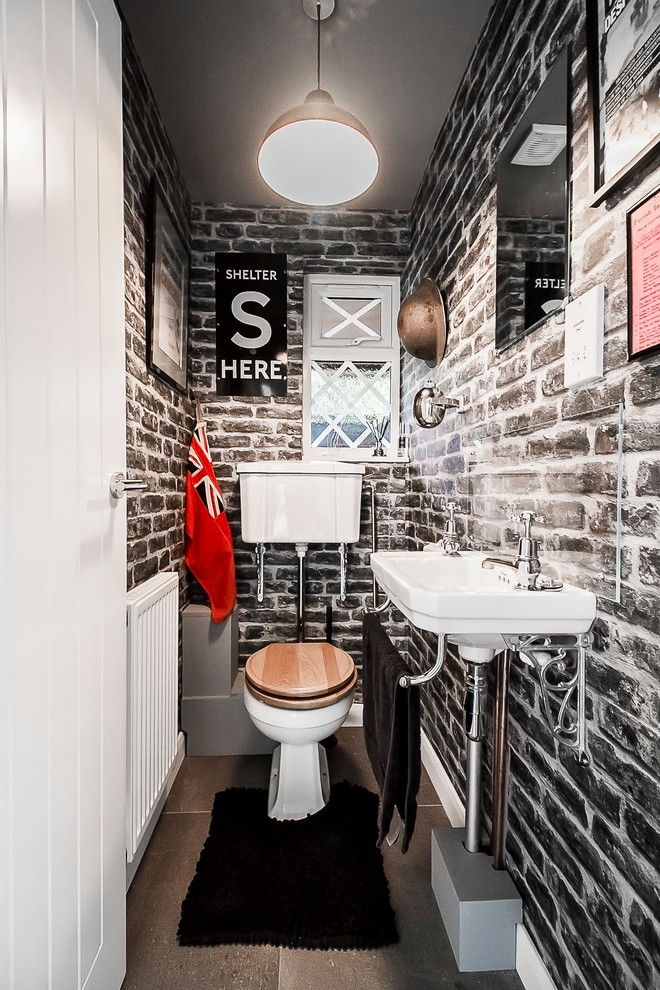 Small eclectic brown tile slate floor and gray floor powder room photo in London with a one-piece toilet, white walls and a wall-mount sink
