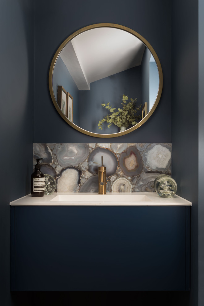 Inspiration for a small contemporary multicolored tile powder room remodel in London with flat-panel cabinets, blue cabinets, gray walls, an undermount sink and white countertops