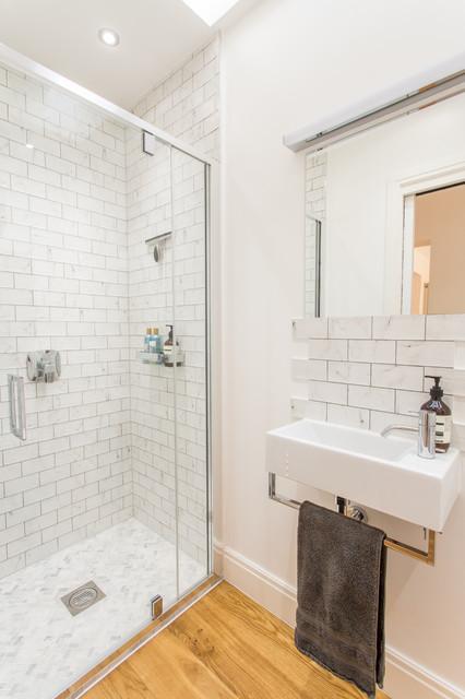 Cette image montre un petit WC et toilettes design avec un WC suspendu, des carreaux de céramique, un mur blanc, un sol en bois brun, un lavabo suspendu et un carrelage blanc.