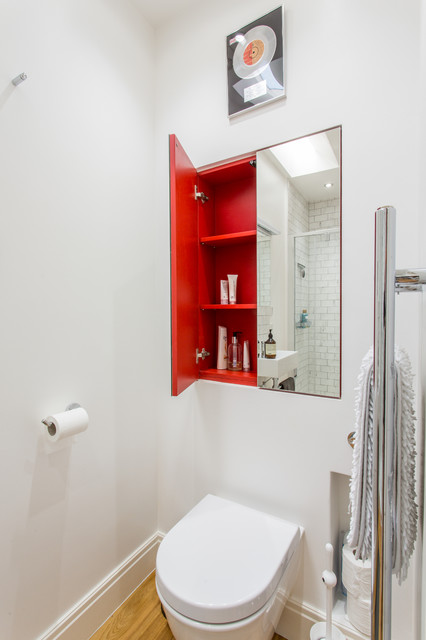 Small contemporary cloakroom in Other with a wall mounted toilet, white walls and medium hardwood flooring.