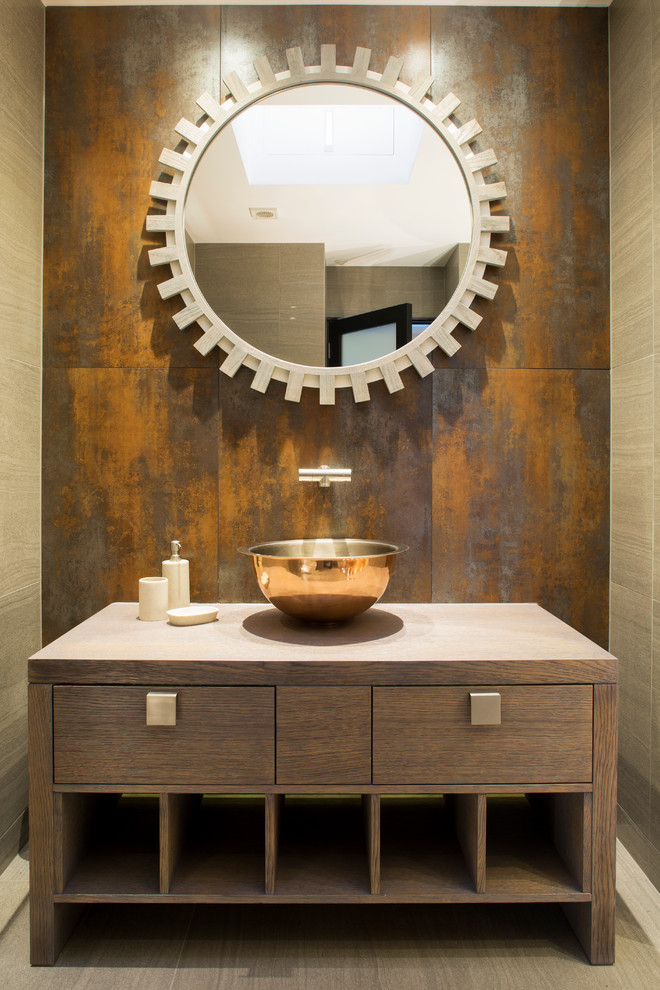 Example of a trendy powder room design in London with a vessel sink, furniture-like cabinets, medium tone wood cabinets, wood countertops and brown countertops