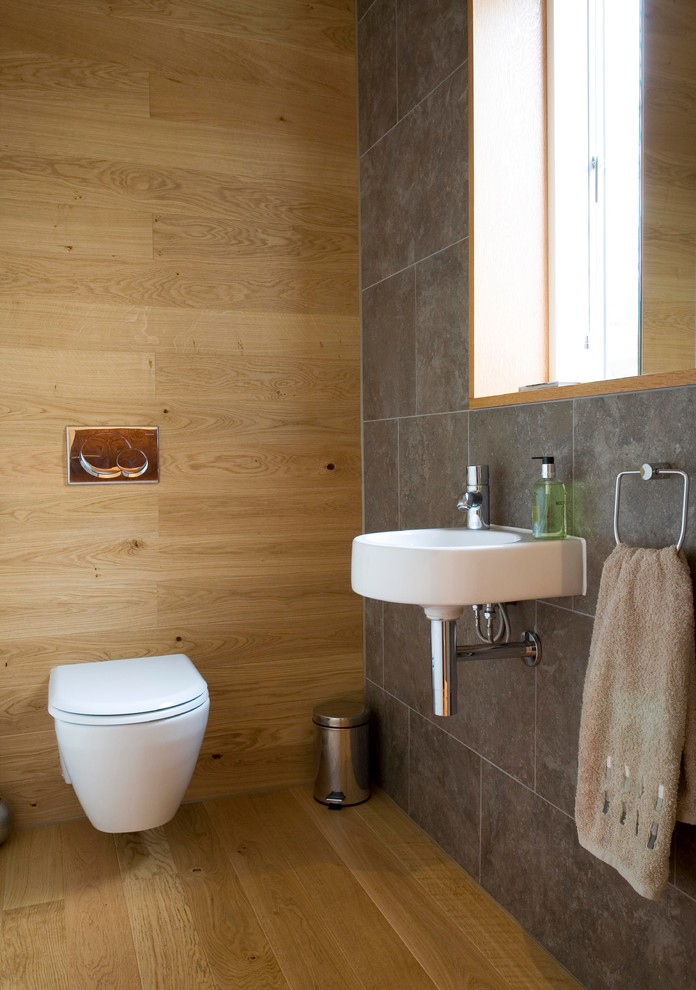 Small trendy porcelain tile and gray tile light wood floor powder room photo in Edinburgh with a wall-mount sink and a wall-mount toilet