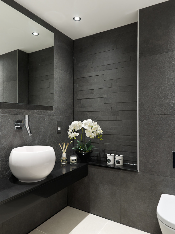 Example of a trendy gray tile and black tile powder room design in Surrey with a vessel sink, a wall-mount toilet, gray walls and black countertops