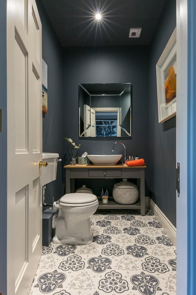 Idee per un bagno di servizio contemporaneo di medie dimensioni con nessun'anta, ante grigie, WC a due pezzi, pareti grigie, pavimento in cementine, top in legno, pavimento multicolore e top marrone