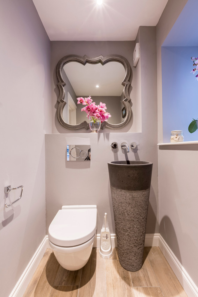 Example of a transitional light wood floor powder room design in London with a wall-mount toilet, gray walls and an integrated sink