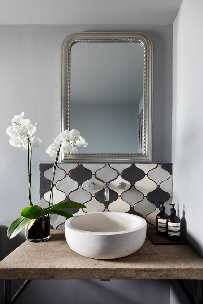 Inspiration for a small mediterranean ceramic tile and gray tile powder room remodel in London with gray walls, concrete countertops, furniture-like cabinets, gray cabinets, a vessel sink and beige countertops