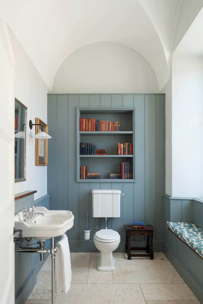 Example of a small classic beige floor powder room design in London with a two-piece toilet, multicolored walls, a console sink and blue cabinets