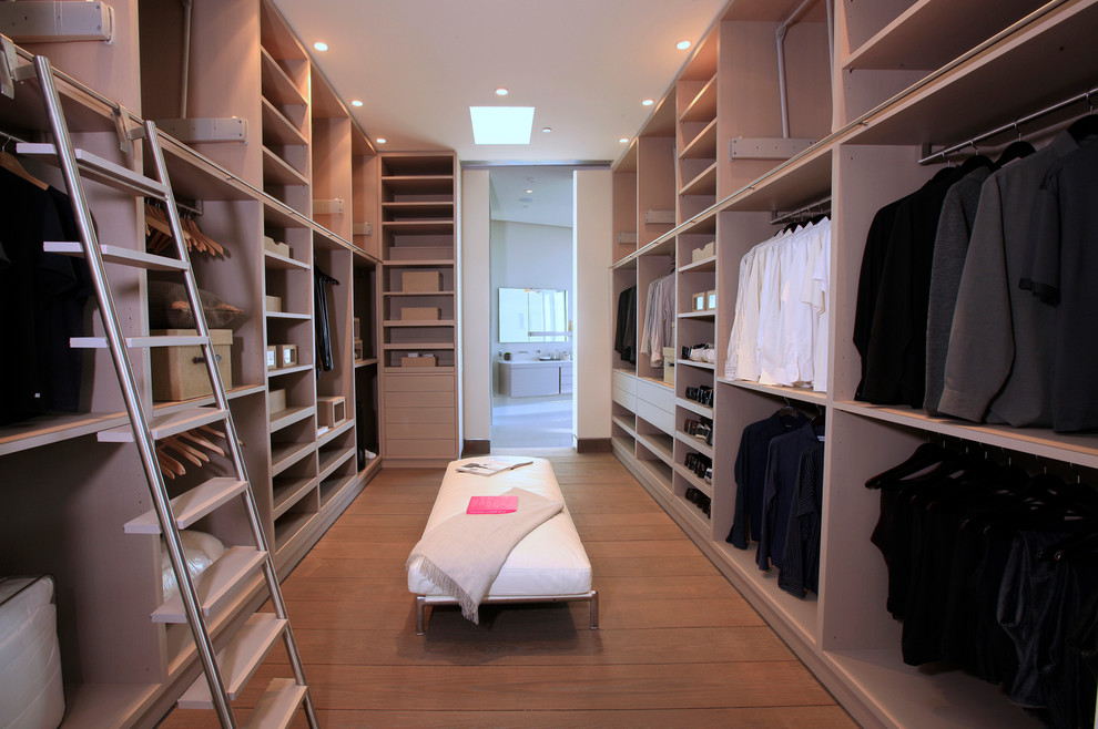 Example of a trendy men's dressing room design in Los Angeles with open cabinets and light wood cabinets