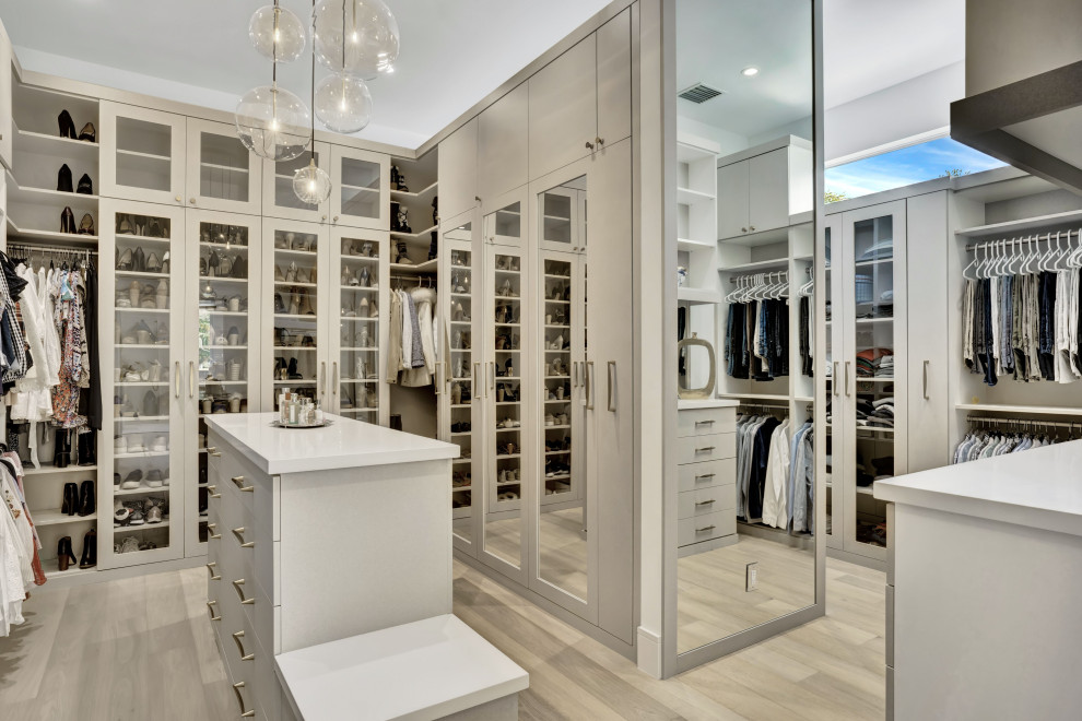 Example of a large trendy gender-neutral light wood floor and beige floor walk-in closet design in Miami with glass-front cabinets and gray cabinets