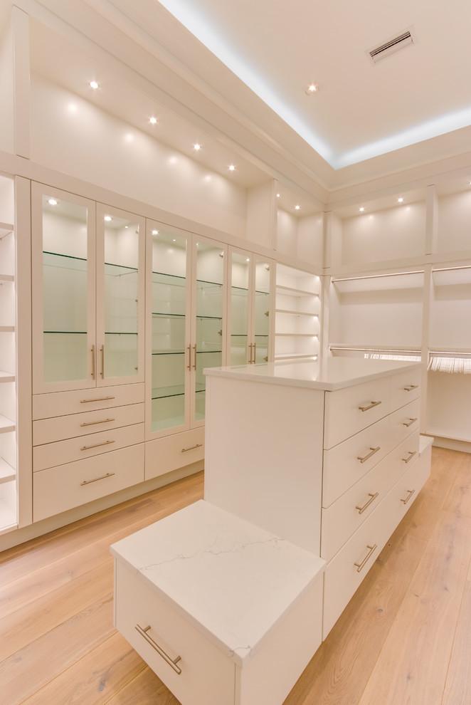 Diseño de armario vestidor de mujer, clásico renovado, grande, con armarios con paneles lisos, puertas de armario blancas, suelo de madera en tonos medios y suelo marrón
