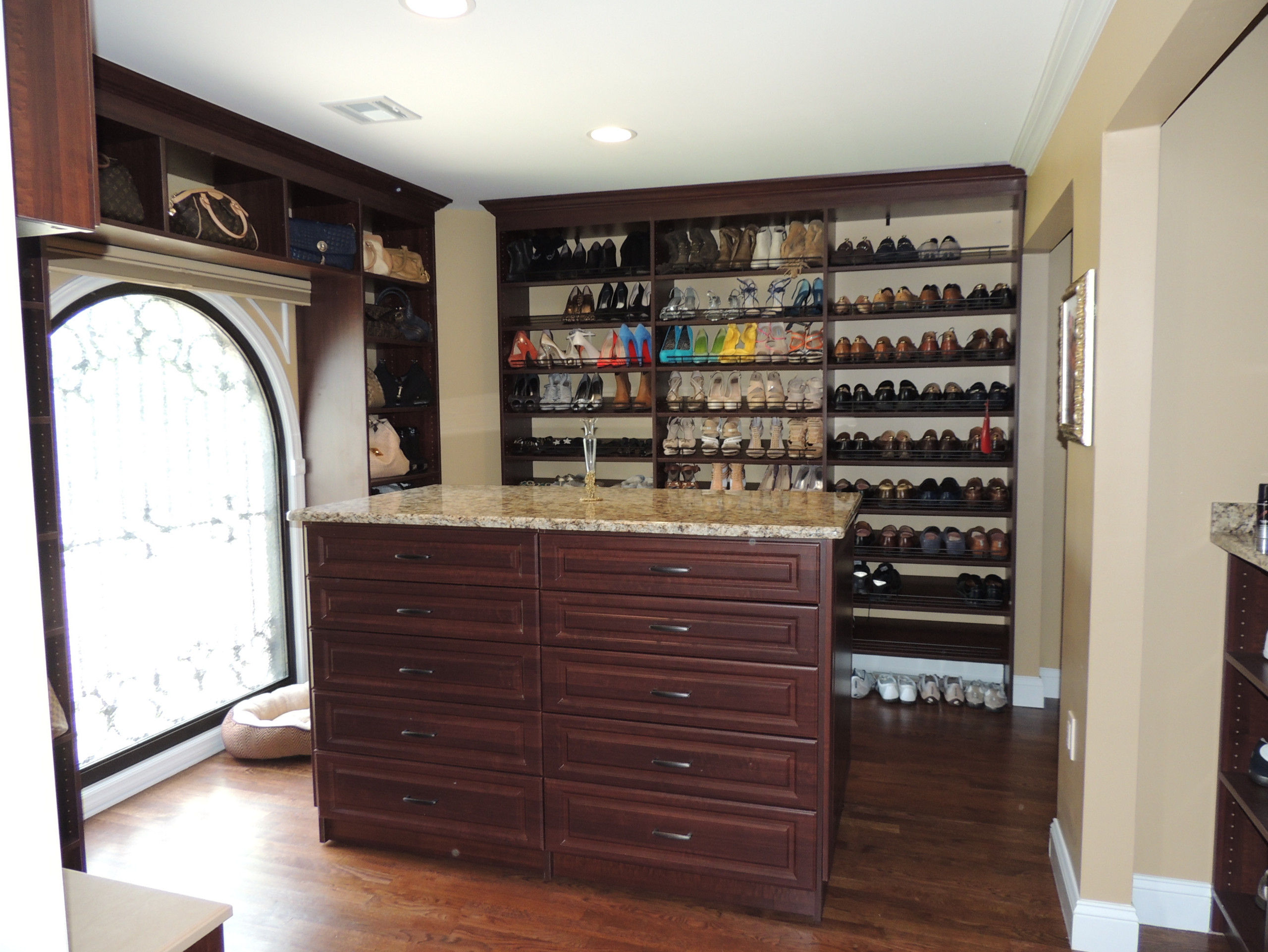 Closet has a large window and the clients wanted to have shelving to go around the window.  There is a large island with twenty drawers.  All the drawers have custom jewelry, tie and dividers.  There