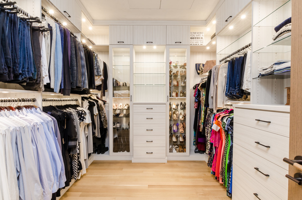 Example of a huge trendy gender-neutral light wood floor walk-in closet design in New York with light wood cabinets