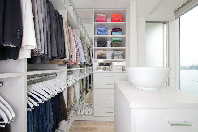 Example of a large minimalist gender-neutral light wood floor and beige floor dressing room design in Jacksonville with flat-panel cabinets and white cabinets