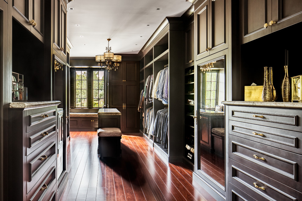 Inspiration for a large timeless men's medium tone wood floor walk-in closet remodel in New York with dark wood cabinets and recessed-panel cabinets