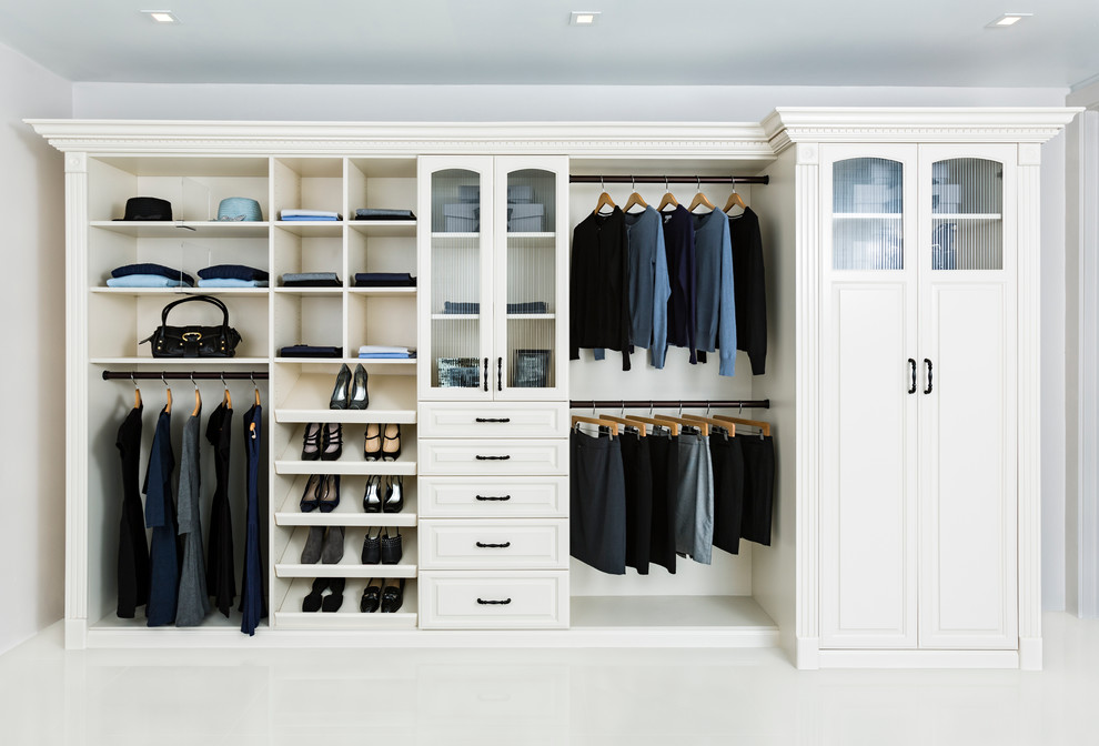 Example of a large classic gender-neutral white floor reach-in closet design in Los Angeles with white cabinets and raised-panel cabinets