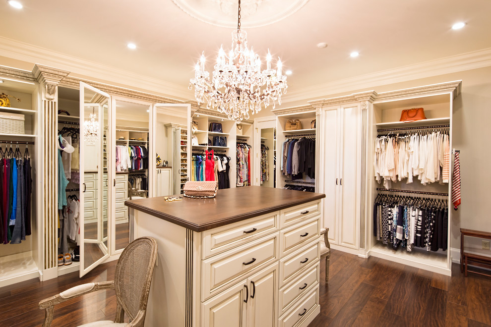 Walk-in closet - large traditional women's dark wood floor and brown floor walk-in closet idea in Los Angeles with white cabinets and raised-panel cabinets