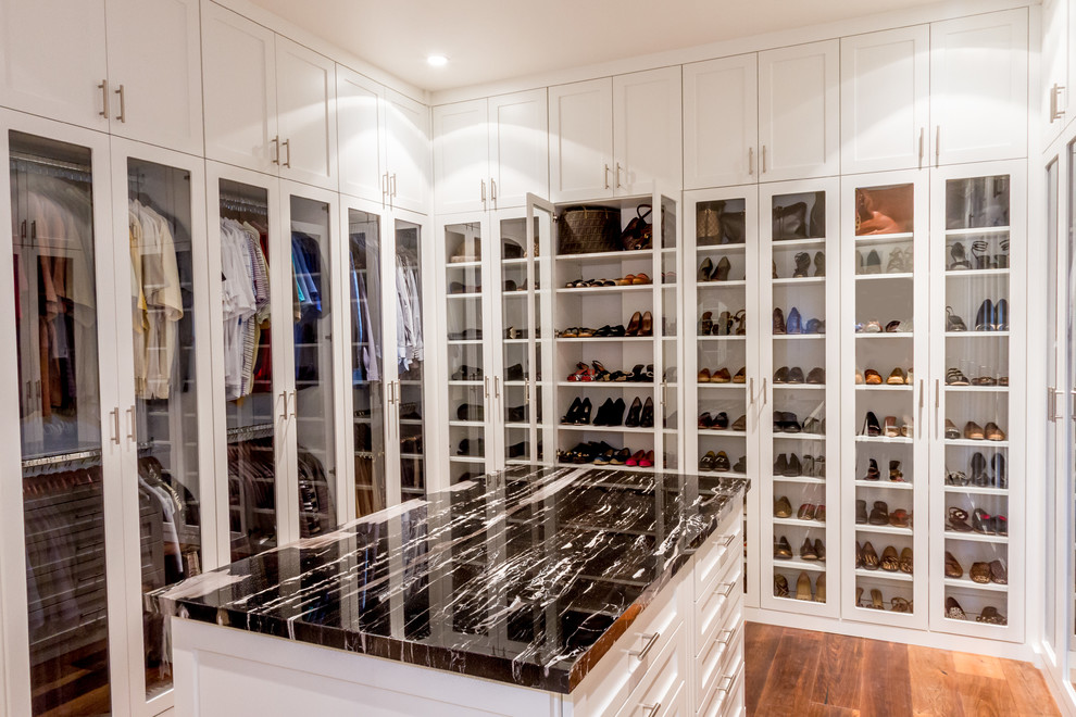Trendy gender-neutral medium tone wood floor and brown floor walk-in closet photo in Minneapolis with glass-front cabinets and white cabinets