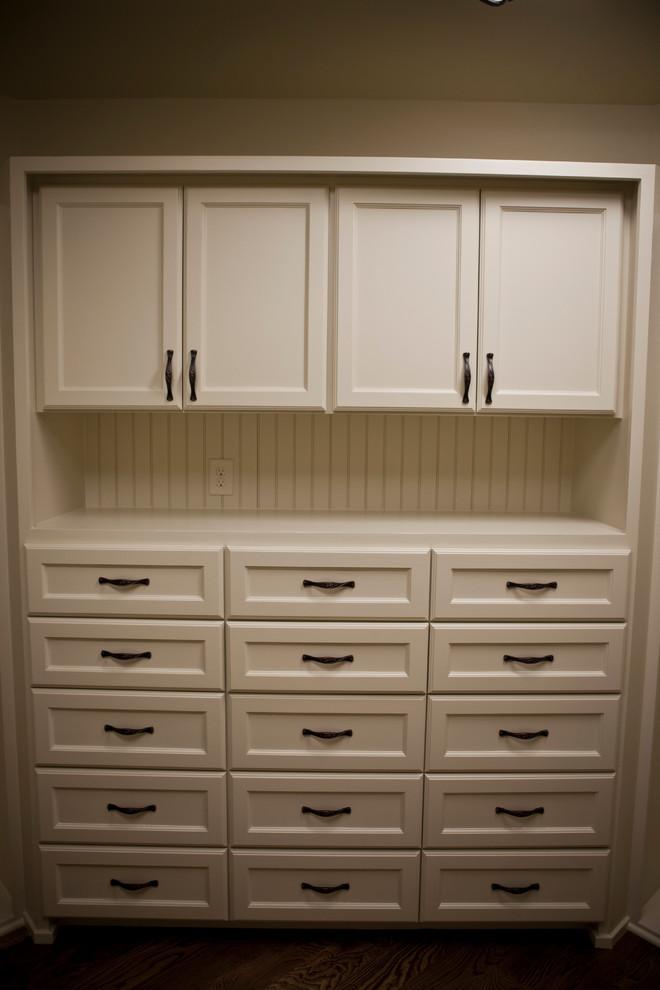Modelo de armario vestidor de mujer, rústico, grande, con puertas de armario blancas, suelo de madera en tonos medios y armarios con paneles empotrados
