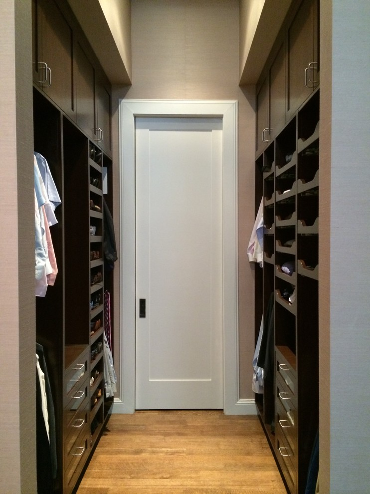 Mid-sized elegant men's medium tone wood floor dressing room photo in New York with recessed-panel cabinets and dark wood cabinets