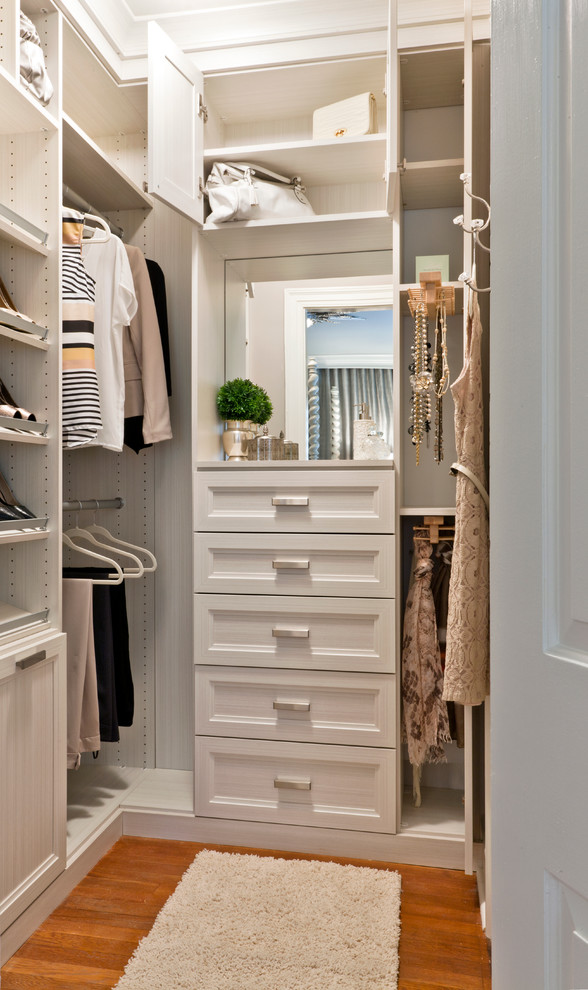 Transitional women's medium tone wood floor walk-in closet photo in Other with recessed-panel cabinets and white cabinets
