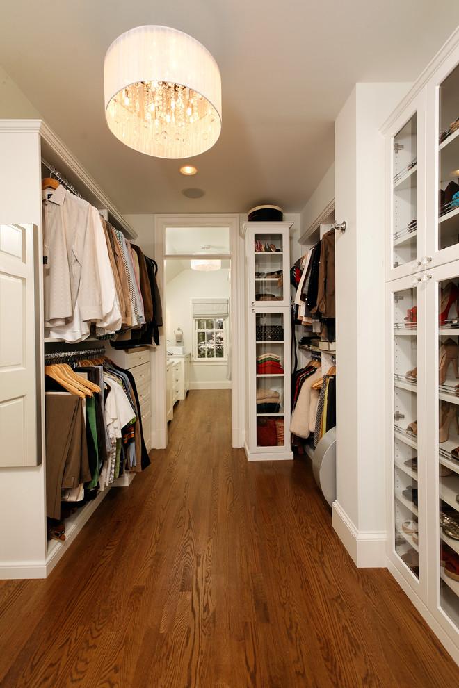 Example of a classic medium tone wood floor closet design in DC Metro with white cabinets