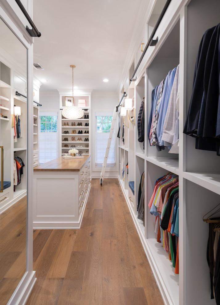 Inspiration for a country gender-neutral medium tone wood floor and brown floor dressing room remodel in Houston with open cabinets and white cabinets